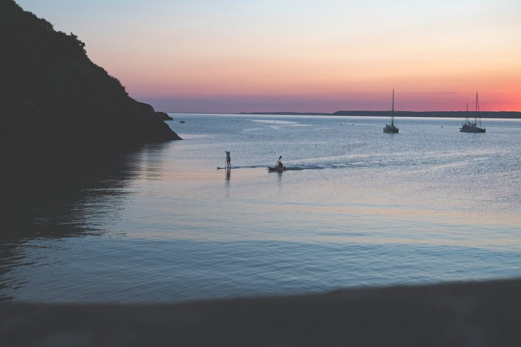 Paddlers in the sea by Hope Cove House